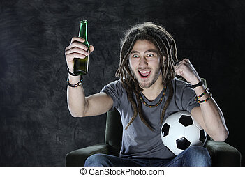 Football or soccer fan watching television - Young adult man...