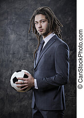 Young businessman with a soccer ball