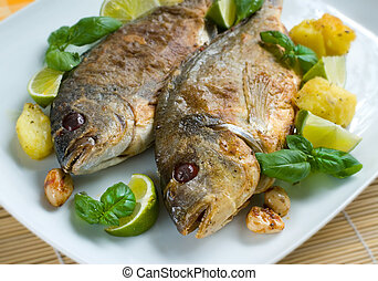 Baked gilt-head garnished with fresh basil leaves and green...