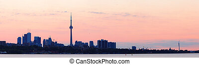 Toronto sunrise silhouette over lake with red tone