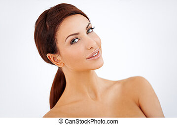 Smiling woman with naked shoulders - Tilted view studio...