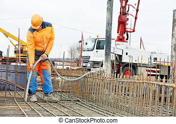 builder worker vibrating concrete in form - builder worker...