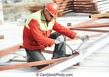 builder worker assembling metal construction - builder...