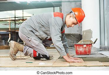tiler at industrial floor tiling renovation work -...