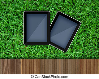 Tablet pc computer on grass field