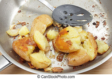 Crushed garlic potatoes in the pan - A frying pan with...