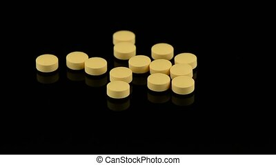 Pills rotating on black reflective background