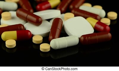 Pills rotating on black reflective background.