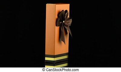 Orange box with gold bow on black background