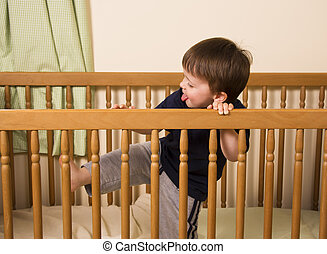 Toddler climbing out of cot - A stock photo of a toddler...