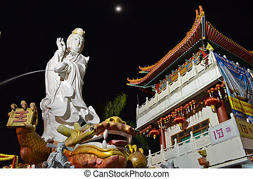 Guan Yin Statue On Night Time With Crescent Moon Of Thailand...