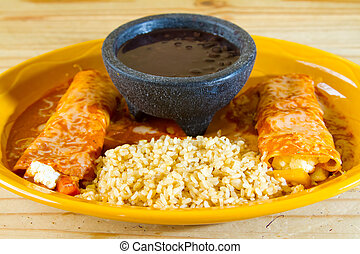 Mexican Restaurant Food - Enchiladas and rice and beans at a...