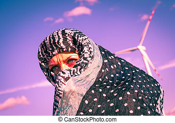 Muslim girl and windturbine in the background - An image of...