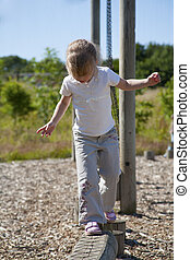 young girl on wooden balance beam at playground