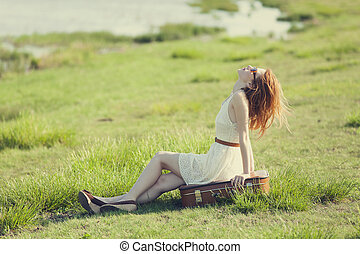 Young fashion girl with suitcase sitting at spring grass...