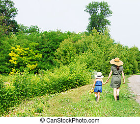 Happy mother and her little daughter walking near country...