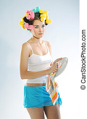 A woman in hair curlers is drying up the plate