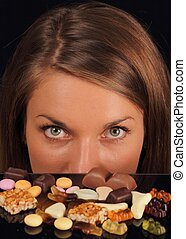 Attractive woman over sweets looking in camera - Young...