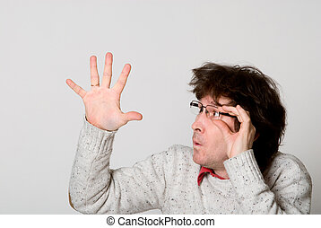 Man with disheveled hair pointing hand at something...