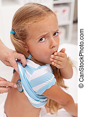 Coughing little girl at the doctors being checked with...