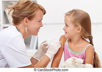 Brave little girl receiving injection or vaccine with a...