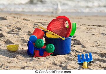Beach Toys - A blue pail full of toys on a sandy beach with...