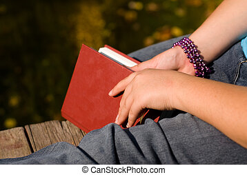 Quiet Time - Closeup of a book and a girls leg, symbolizing...