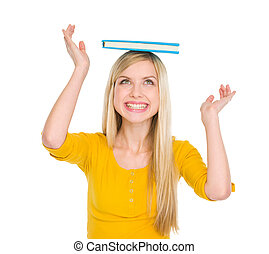 Happy student girl balancing book on head