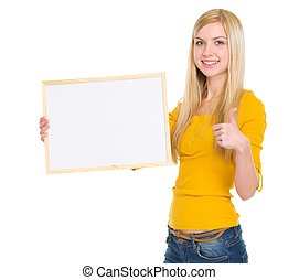Happy student girl showing blank board and thumbs up