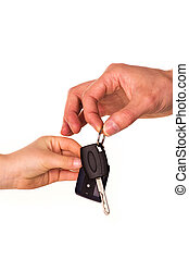 Male hand holding a car key and handing it over to another...