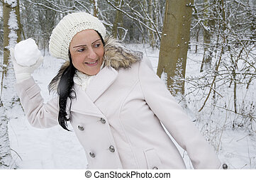woman throwing snowball in snow covered forest