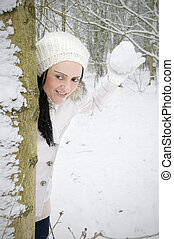 woman hiding behind tree throwing snowball in snow covered...