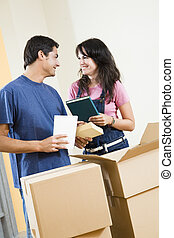 new house - Young happy couple moving boxes at home