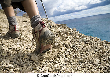 hiking - young woman hiking on a cliff near the sea