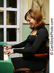 Pregnant woman plays on the piano - The pregnant woman plays...