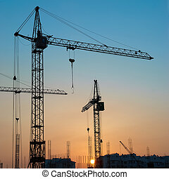 Industrial cranes - Industrial landscape with silhouettes of...