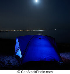 Blue illuminated tent at night on the beach Moon, stars and...