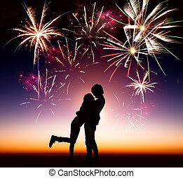 happy young couple with fireworks background