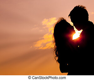 Romantic lovers hugging at twlilight with sunset in...
