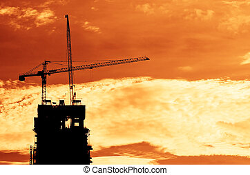 Industrial construction cranes and building   at sunrise.