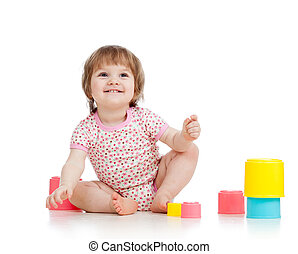 Cute baby girl playing with toys while sitting on floor,...