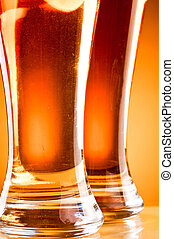 Bottom of two glass beer over yellow background