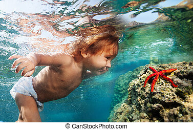 Discovering underwater treasures - Two years old boy diving...