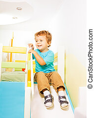 Little boy sliding from slide at his bedroom second story...