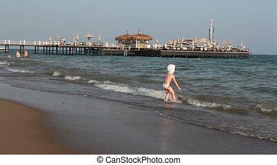 little girl runs into the sea