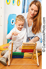 Teaching math - Mother and her little son learning math with...