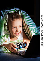 Hide from mom, play games - Young five years old boy hiding...