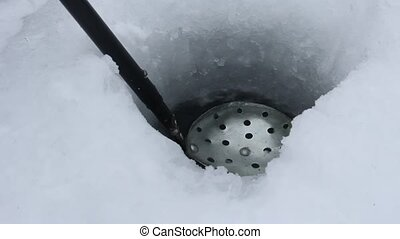 ice fishing scoop - scooping ice out of an ice fishing hole