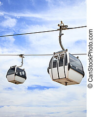 Two cable car on a partly cloudy sky background - A cablaway...
