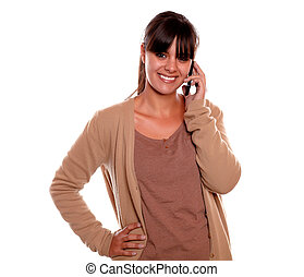 Charming young woman conversing on cellphone